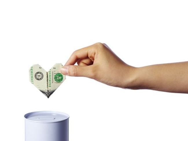 Donors Giving Less - Hand Putting Dollar in Can