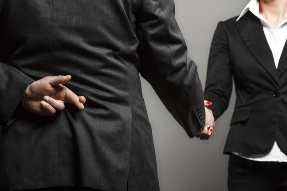 picture of businessman shaking hands with businesswoman with his fingers crossed behind his back organization