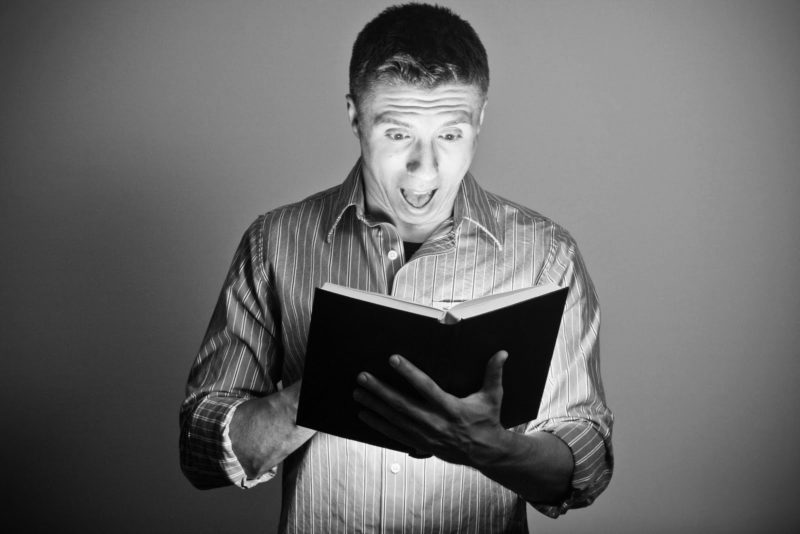 man reading a book with surprise
